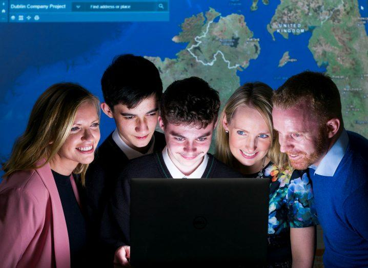 Two women, two boys and a male teacher look into a laptop screen with a map in background.
