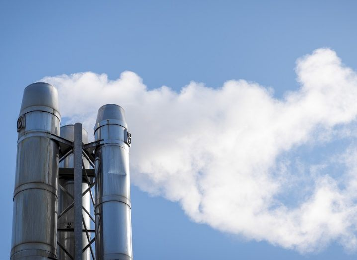 Smoke coming from a stack of multiple steel chimneys against a blue sky.
