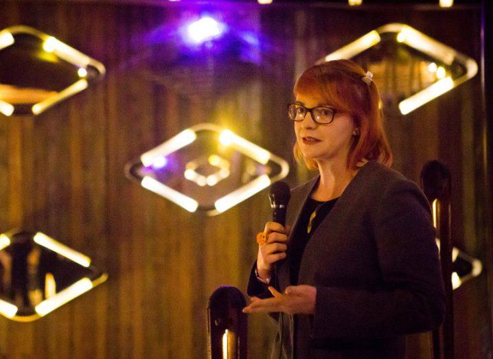 A woman with red hair and glasses gestures while speaking into a microphone in front of a backdrop of diamond-shaped lights.