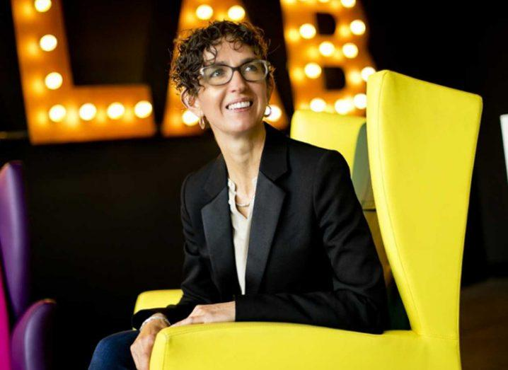 woman in glasses in dark jacket smiles while sitting in a yellow chair.
