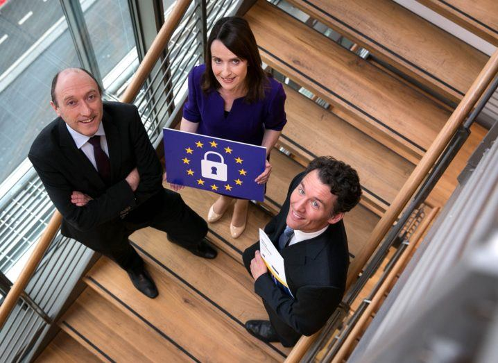 Two men and a woman on a stairwell holding an EU flag with a lock at centre.