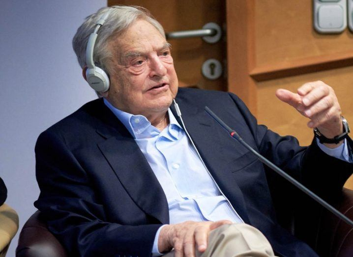 George Soros in a navy blazer and blue shirt sitting down and speaking at an event.