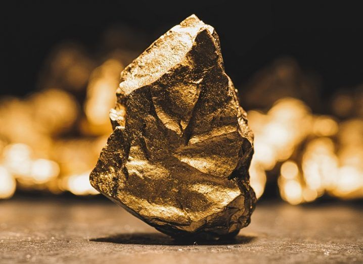 Big gold nugget in front of a mound of gold.