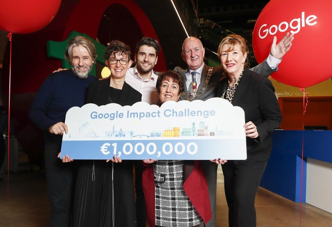 Group of people - three men and three women - hold up a Google signing that reads one million euro Google Impact Challenge.