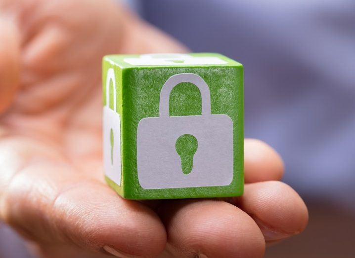 Close-up of hand holding green wooden block with white lock symbol on it.