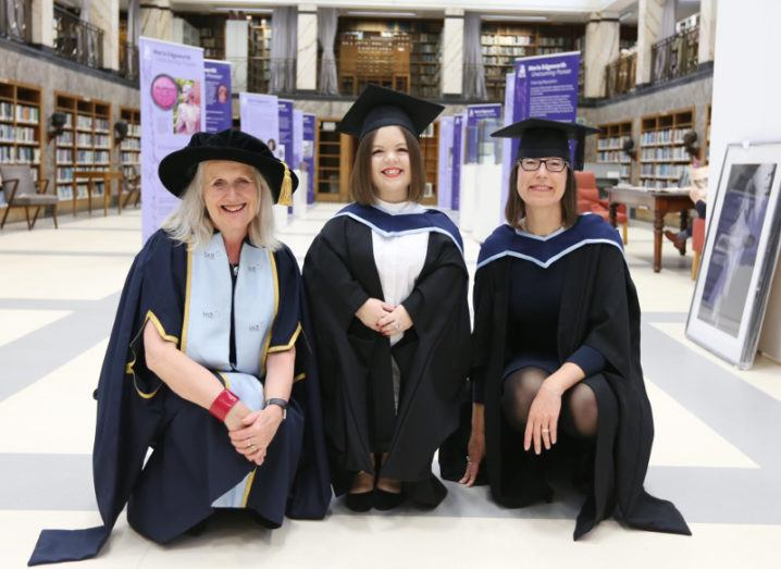 three women in academic cap and gowns.