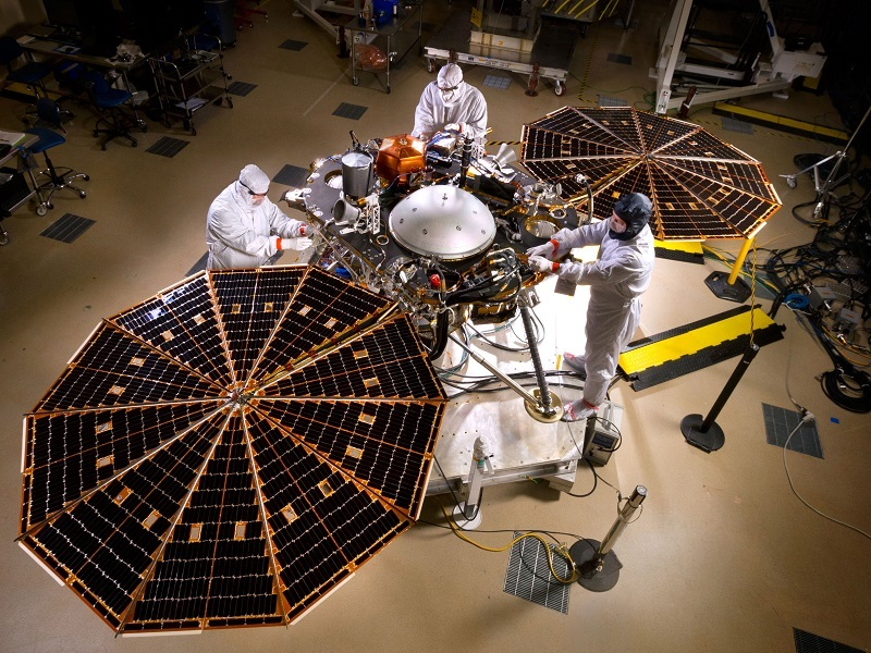 Engineers in white jumpsuits working on the InSight lander with solar arrays open.