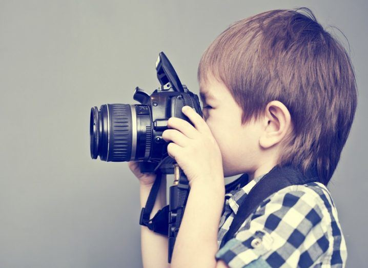 Small boy with brown hair facing left and taking a photo with a camera.