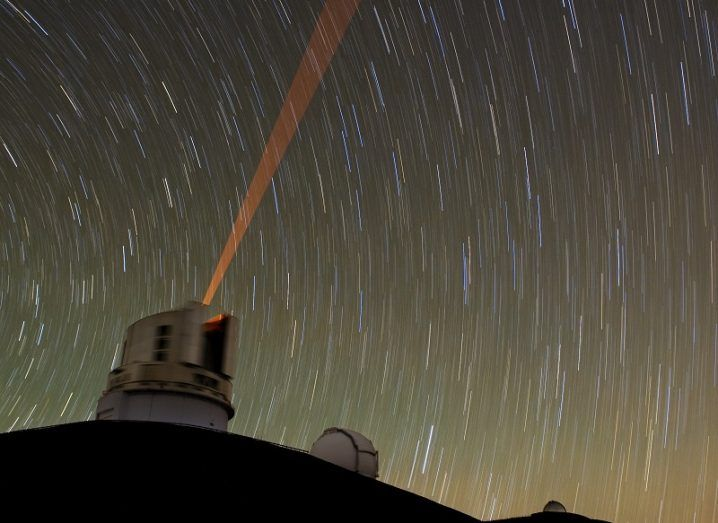 Time-lapse shot of moving stars with a observatory emitting a laser beam in the foreground.