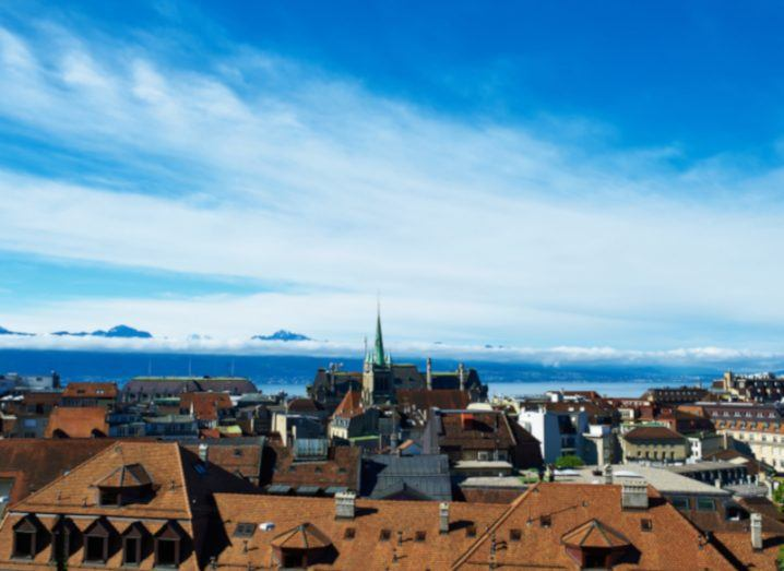 Skyline of Lausanne in Switzerland with Alps in distance.