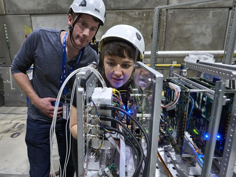 Researchers in safety gear placing Myriad 2 chip in the beam of the particle accelerator, surrounded by electronics.
