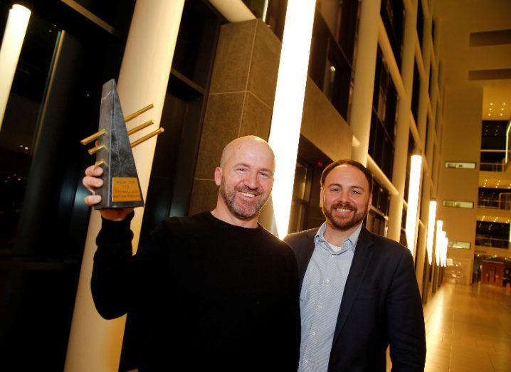 Two men smiling hold aloft a trophy.