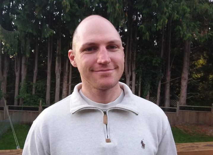 Bald man wearing grey zip-up jacket standing against a backdrop of trees.