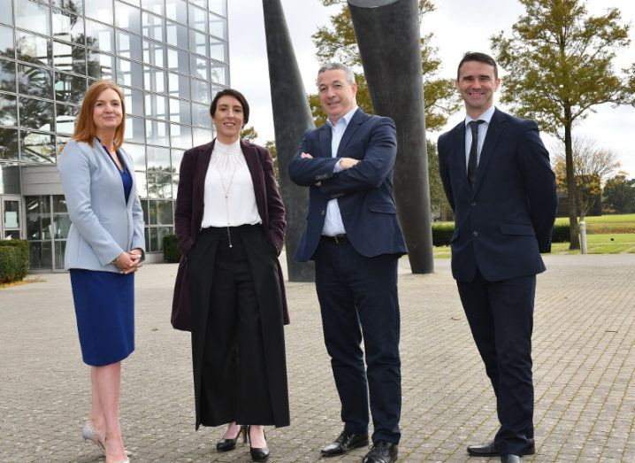 Two women and two men stand outside a glass building with trees around it.