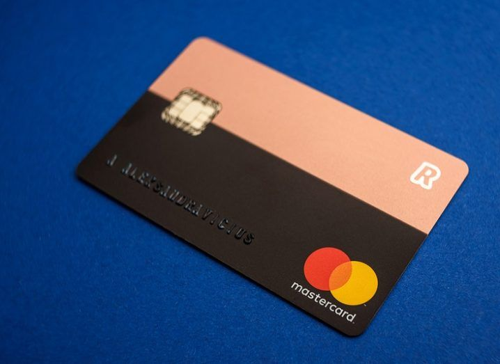 Close-up of a pink and black Revolut debit card against a blue background.