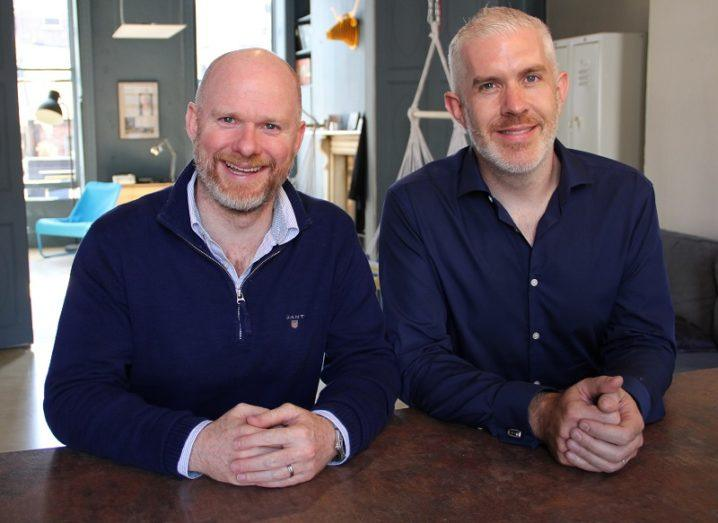 Rubicoin co-founder John Tyrrell and Emmet Savage smiling against an office background.
