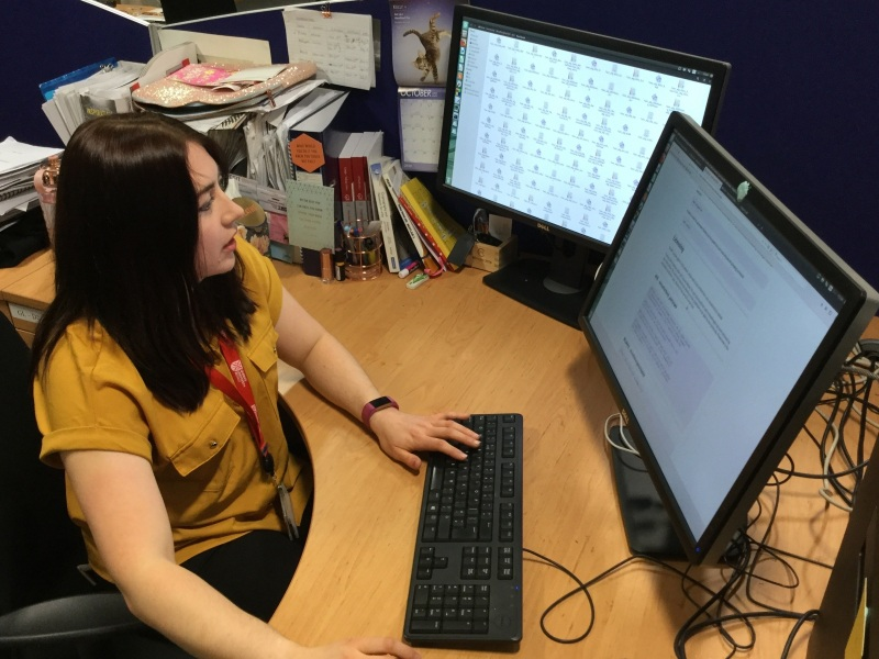 young woman with long dark brown hair wearing short sleeved mustard shirt and red lanyard working in front of two computer screens at a desk.