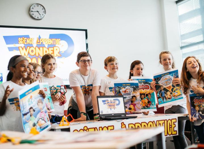 Nine children stand in a row holding up Science Apprentice posters and smiling.