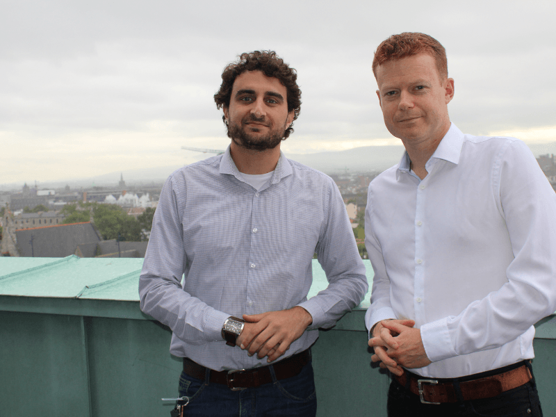 Two men in shirts standing on a rooftop in Dublin.