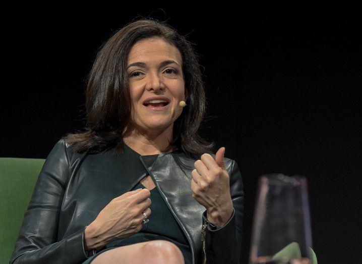 Facebook COO Sheryl Sandberg in a black top, speaking at a conference in Germany.