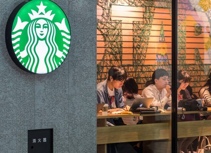 A Starbucks logo beside the front window of the coffee shop with people inside.
