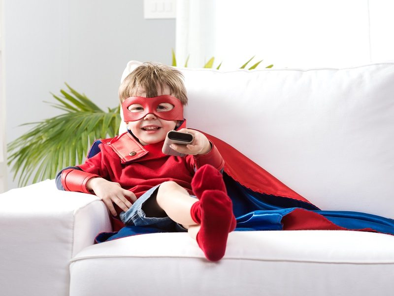 Smiling young boy in a superhero outfit sitting on a couch watching a movie.