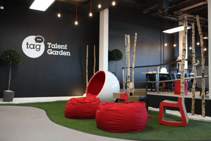 Red beanbags sit on a grass-like floor space. The Talent Garden logo is on the black wall in the background.