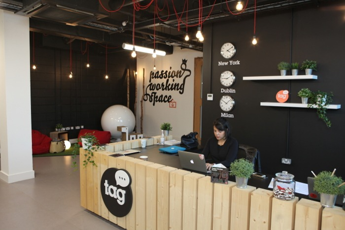 Chic co-working space reception area. The walls are black and there are plants around the reception desk.