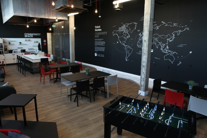 A common area in Talent Garden with a map outline on a wall and table football in the foreground.