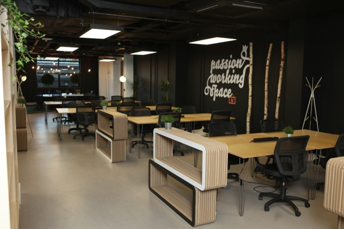 A co-working space in Talent Garden with multiple desks, greenery and soft lighting.