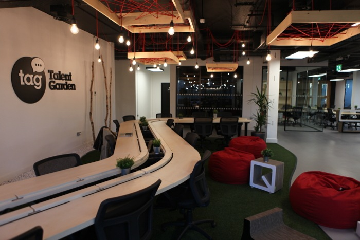 A long desk with multiple chairs with red bean bags around the area.