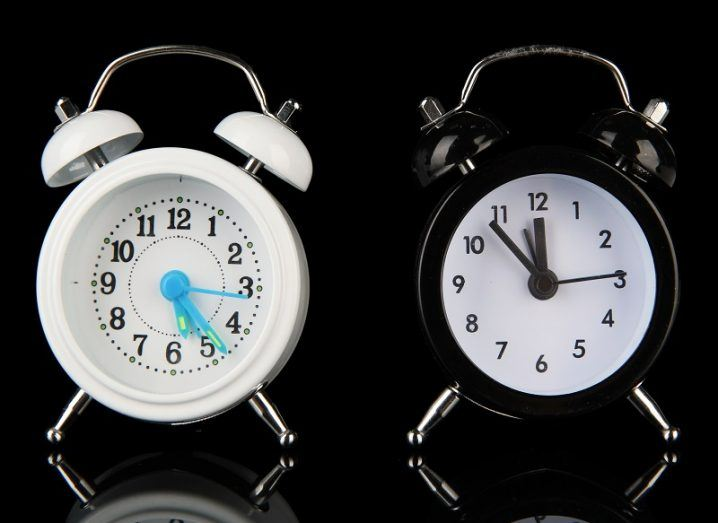 Two old style alarm clocks isolated on black.
