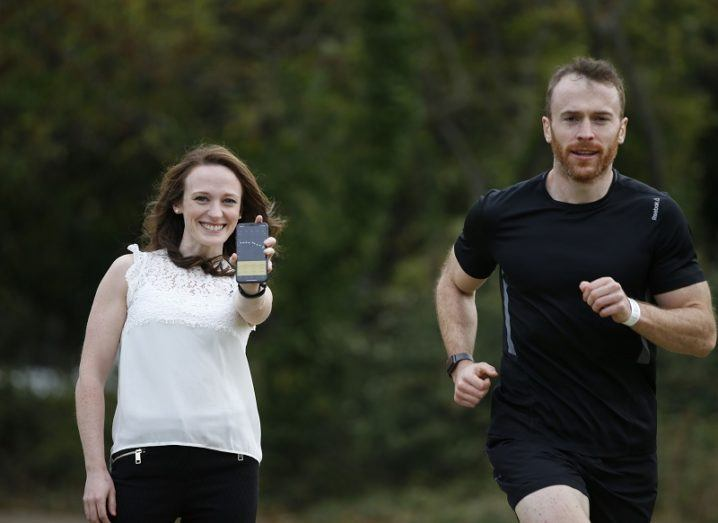Dr Alison Keogh smiling and holding a smartphone with Dr Cailbhe Doherty running past.