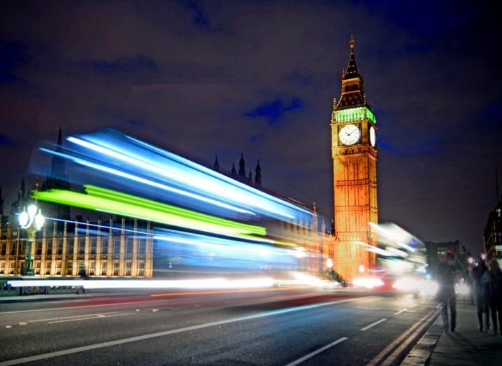 Timelapse shot of a bus driving across London Bridge in front of Big Ben and the UK parliament.