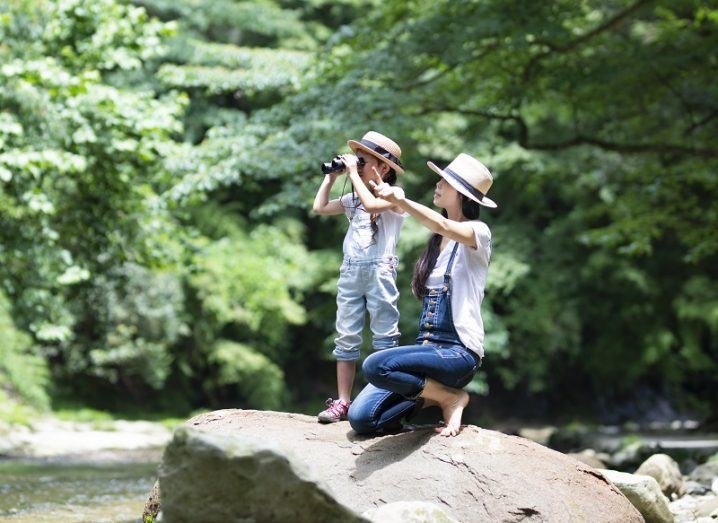 A woman and child are exploring a forest with binoculars.