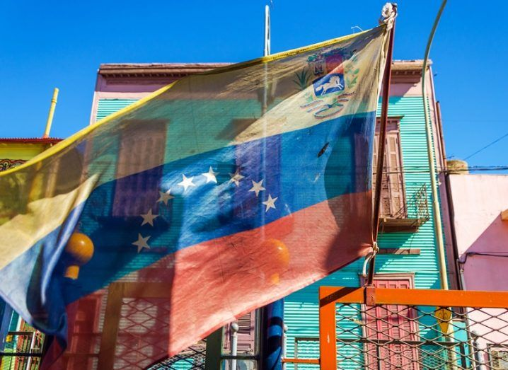 Venezuelan flag blowing in the wind with brightly coloured buildings.