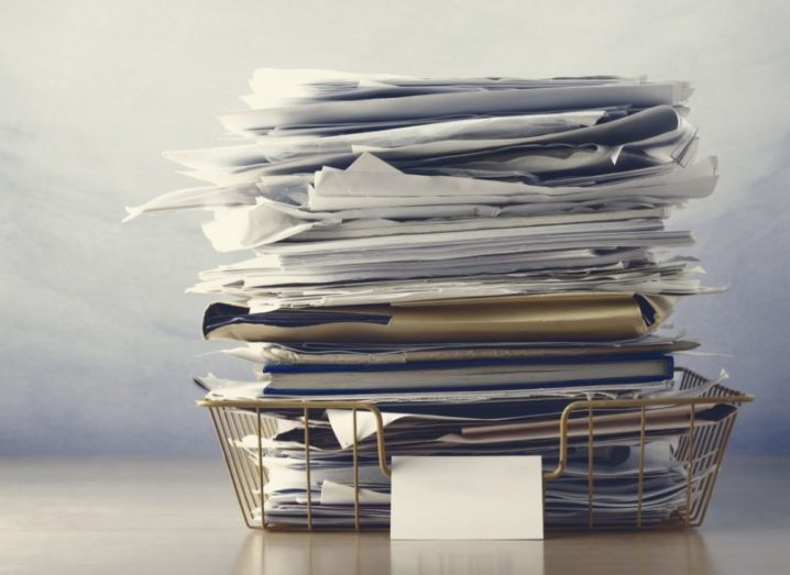 A large pile of files in a wire tray, symbolising an overwhelmed office.