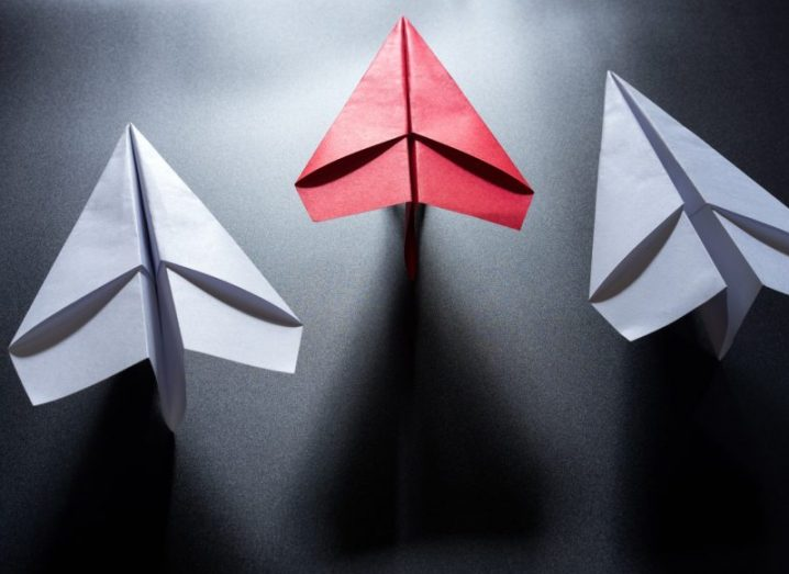 Three paper aeroplanes, two are white while the central one is pink. Marketing email symbol.
