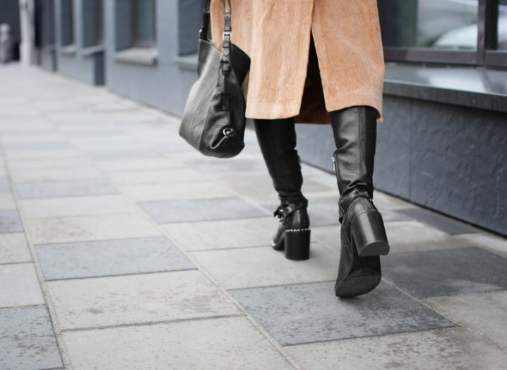 A woman wearing black boots and a camel trench coat walking down a grey city pavement.