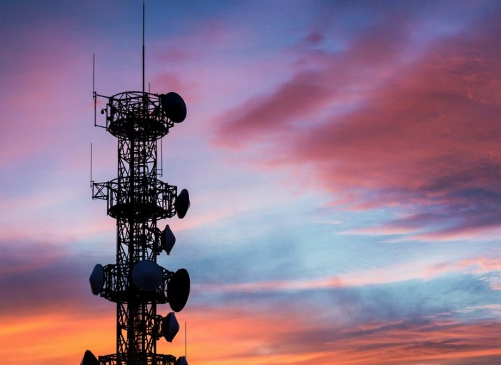 A mobile communication aerial with a pink, blue and orange sunset in the background.