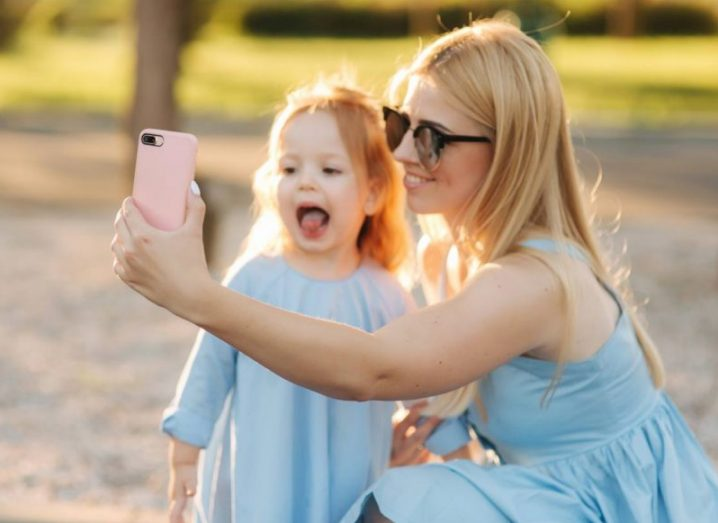 A woman and her young daughter taking a selfie in the park on a sunny evening.