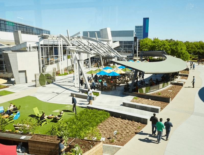 Aerial view of the Googleplex, Google's main campus in Mountain View, California. Employees walking outside.