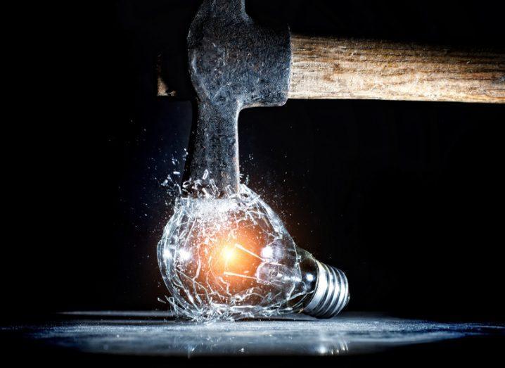 A hammer destroys an electric bulb, symbolising a breakthrough idea.