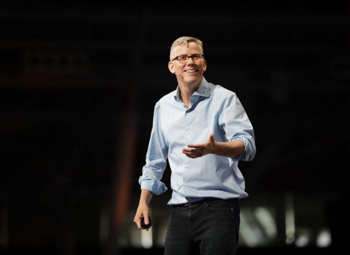 Man in blue shirt and glasses on dark stage.