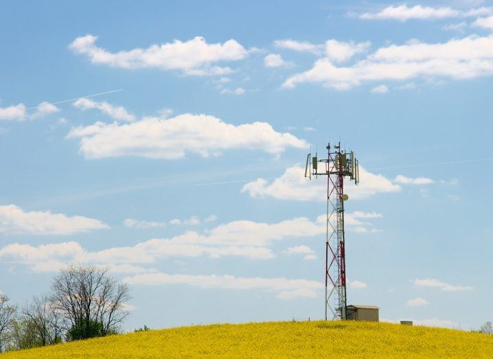 Mobile cell tower standing in a field under a cloudy blue sky.