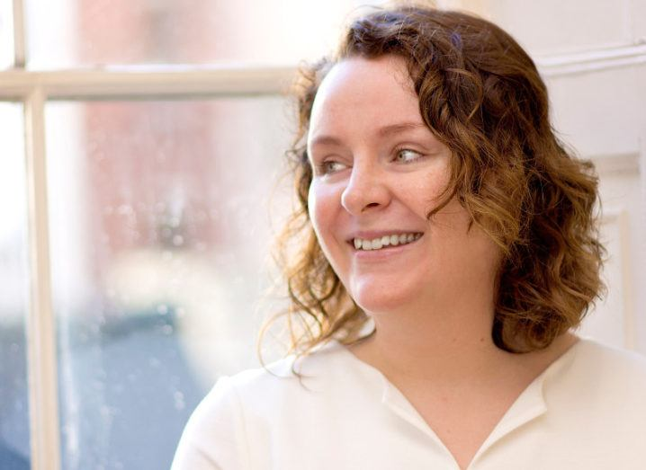 smiling woman with short brown curly hair looking out a window.
