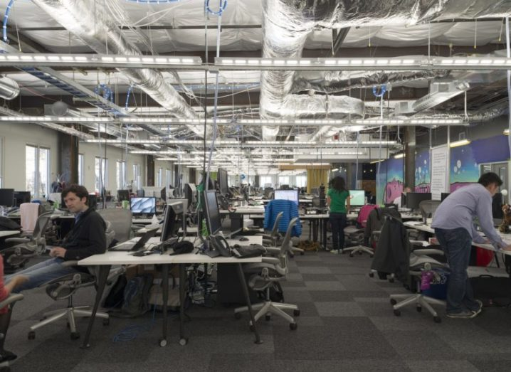 Facebook workers in an open-plan office, with exposed silver ceiling pipes and strip lighting.