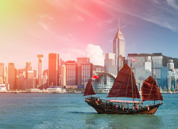 A Chinese junk sails serenely through Hong Kong harbour at sunrise.