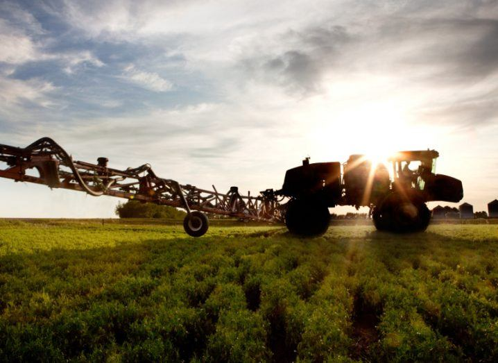 A silhouette of a high clearance sprayer on a field.