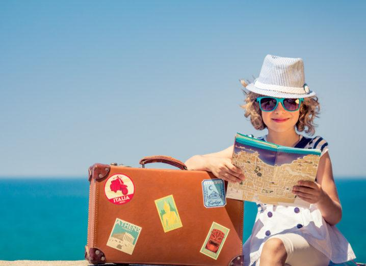 blonde girl wearing sunhat and blue sunglasses reading a map beside a suitcase in front of a blue beach.